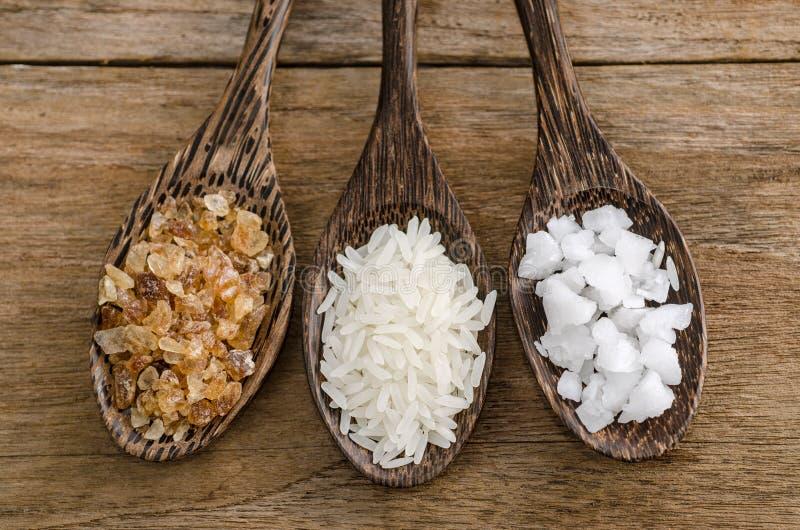 Colher da madeira três com sal, arroz e açúcar cristalino foto de stock royalty free