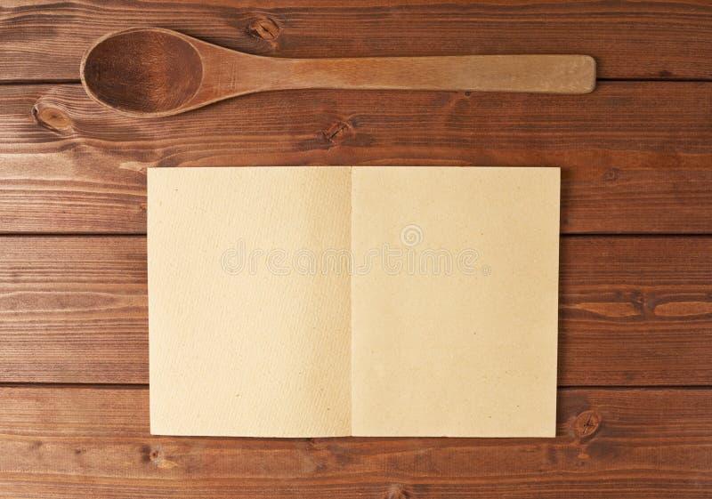 Colher de madeira ao lado do livro da receita fotografia de stock royalty free