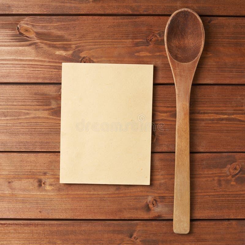 Colher de madeira ao lado do livro da receita imagem de stock royalty free