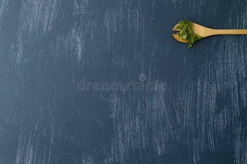 Colher de madeira com coentro fresco no fundo azul imagens de stock