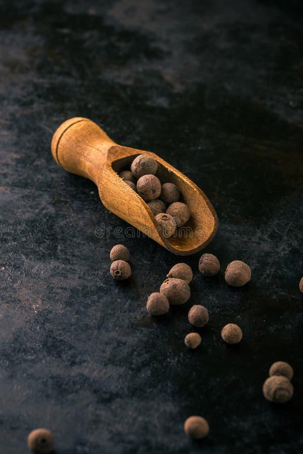 Colher de madeira completamente da pimenta da Jamaica na bandeja da obscuridade do vintage foto de stock royalty free