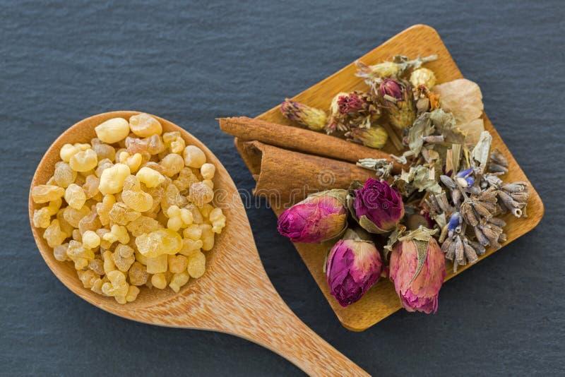 Colher de madeira da goma amarela aromática da resina ao lado das flores secadas fotos de stock royalty free