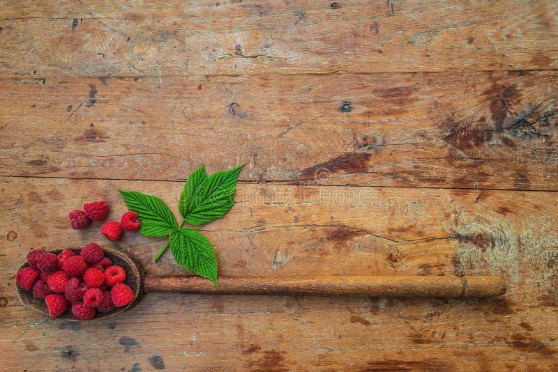 Colher de madeira do vintage com as framboesas vermelhas maduras imagens de stock