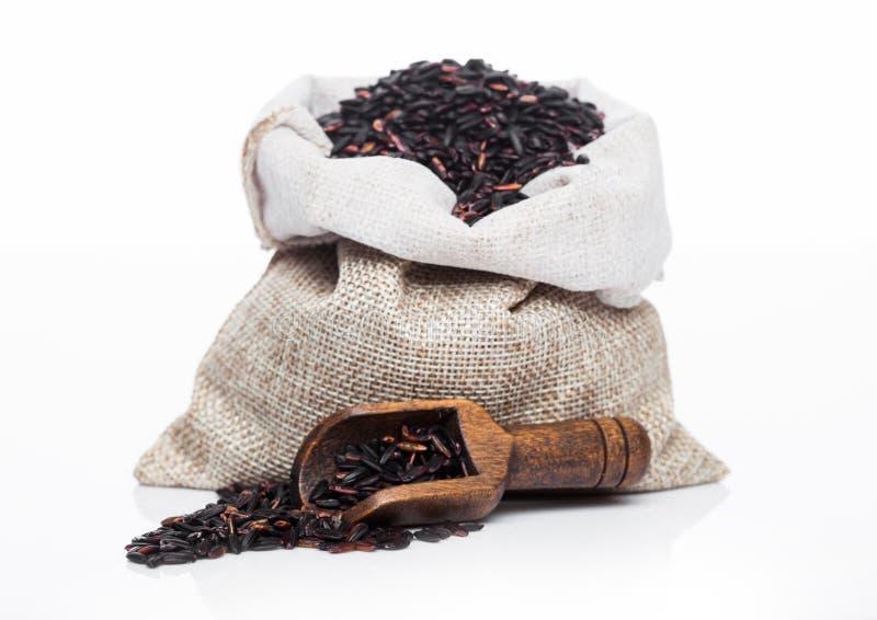Colher de madeira e saco de linho do arroz preto org?nico cru do venus no fundo branco Alimento saud?vel foto de stock royalty free