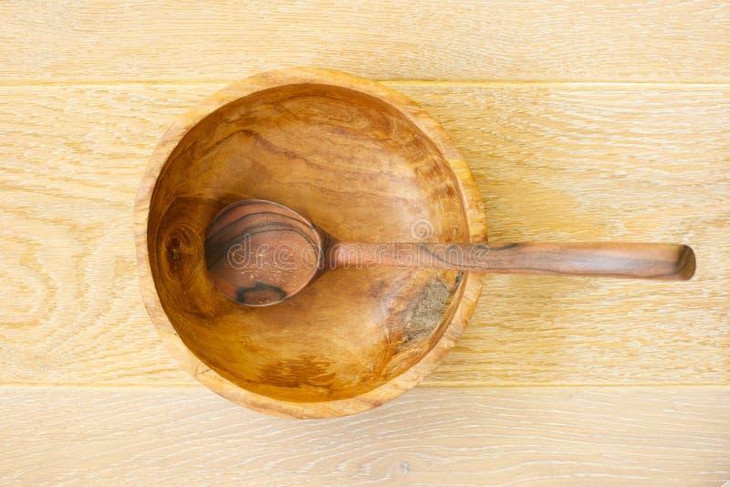 Colher de madeira em uma bacia de madeira imagens de stock royalty free