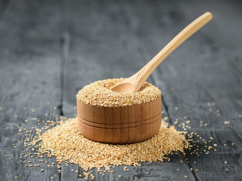 Colher de madeira feita da madeira clara em uma bacia de madeira completamente de sementes do quinoa em uma tabela escura imagens de stock