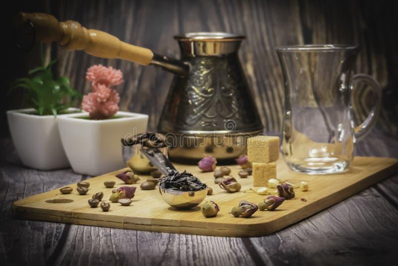 Colher de medição para o chá e o café com feijões de café e as folhas de chá secas em uma placa de madeira fotos de stock
