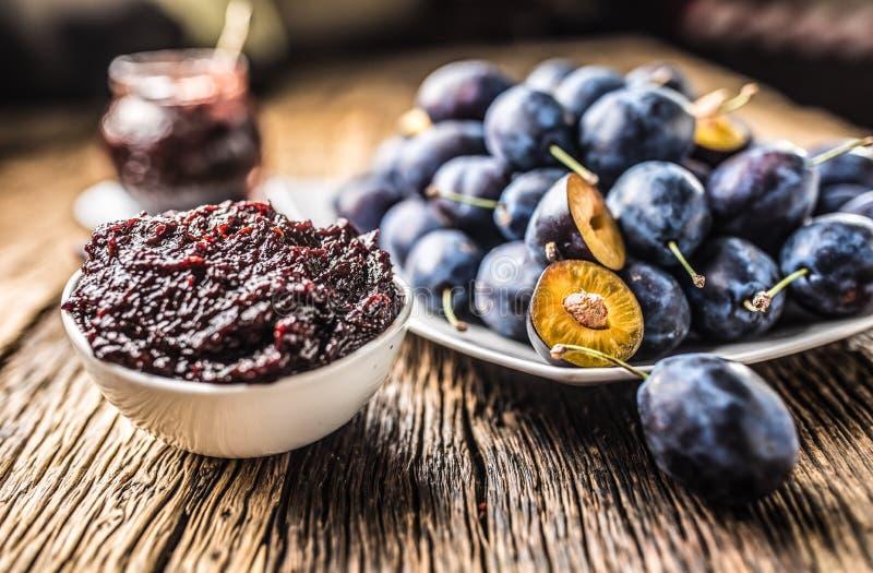 Colher do close-up do doce da ameixa e das ameixas frescas no fundo fotografia de stock royalty free