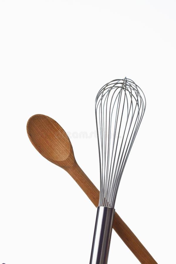 Colher e eggbeater de madeira no fundo branco imagem de stock royalty free
