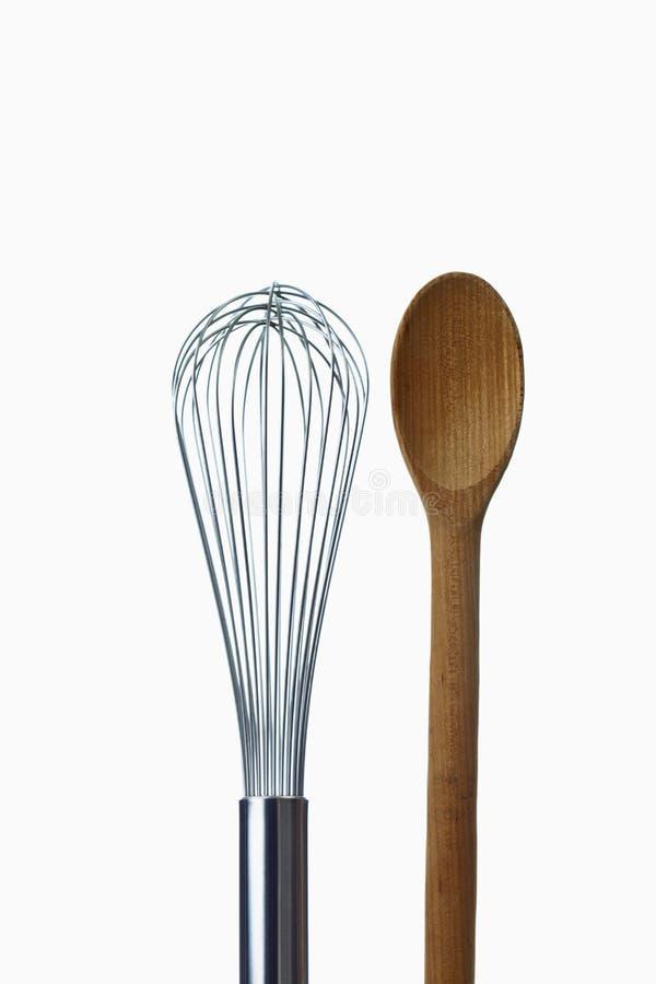 Colher e eggbeater de madeira no fundo branco foto de stock