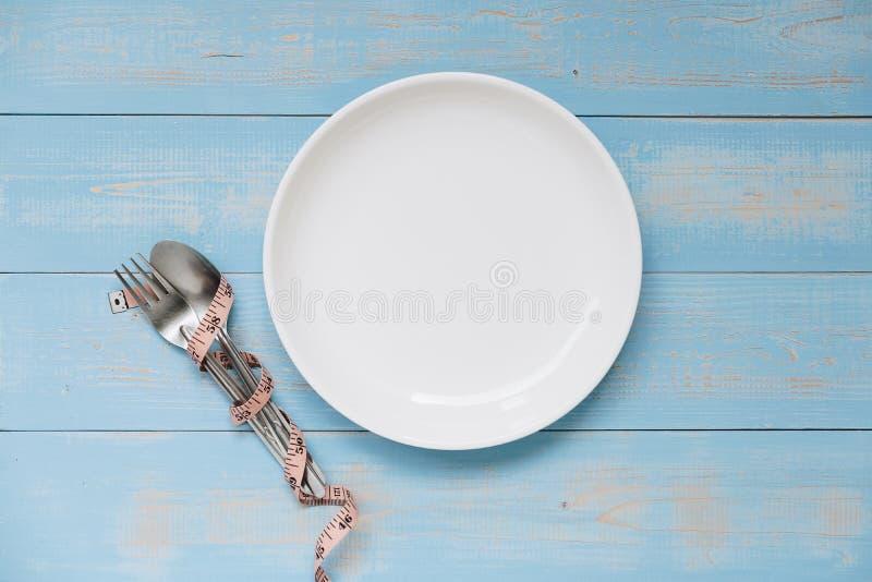 colher e forquilha acima do prato branco com a fita de medição cor-de-rosa na tabela de madeira da cor pastel azul dieta, perda d fotos de stock