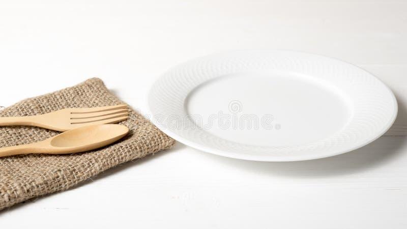 Colher e forquilha de madeira com prato imagens de stock royalty free