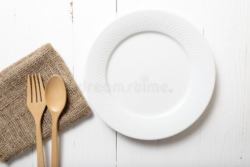 Colher e forquilha de madeira com prato fotografia de stock