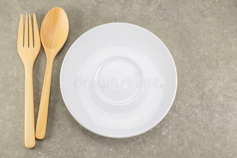 Colher e forquilha de madeira com prato branco fotografia de stock