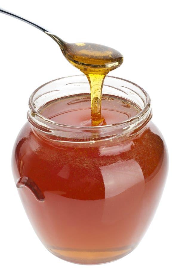 Colher e frasco do mel imagens de stock