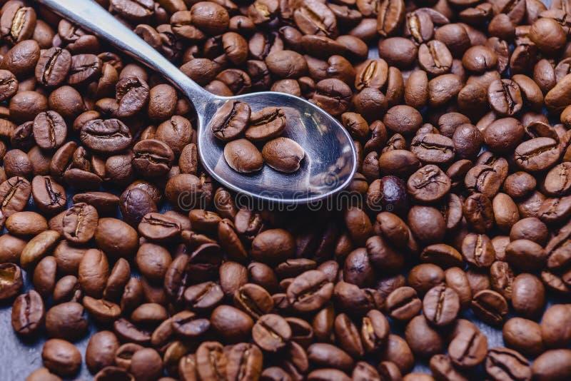 colher em feijões de café no fundo de pedra preto fotografia de stock royalty free