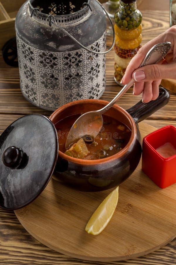 Colher fêmea da terra arrendada da mão da sopa tradicional solyanka do russo com carne fumado no potenciômetro de argila na tabel imagens de stock