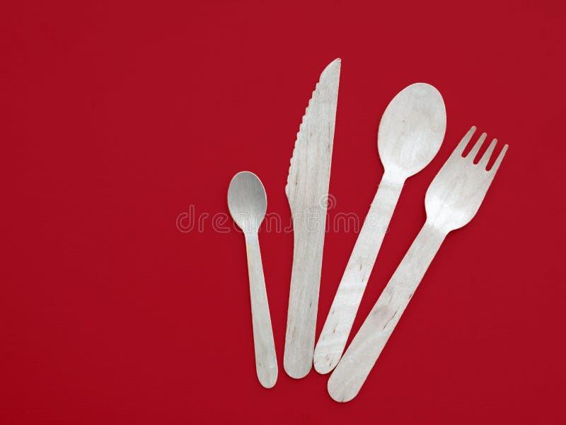 Colher, faca de madeira e forquilha isoladas no fundo branco Cutelaria descartável amigável de Eco no vermelho fotografia de stock royalty free