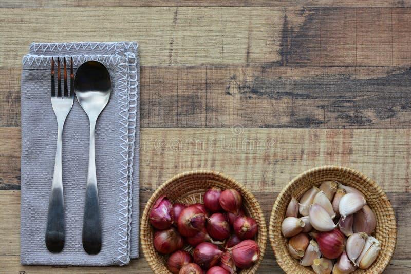 Colher, forquilha, cebola e alho no fundo de madeira marrom imagens de stock royalty free