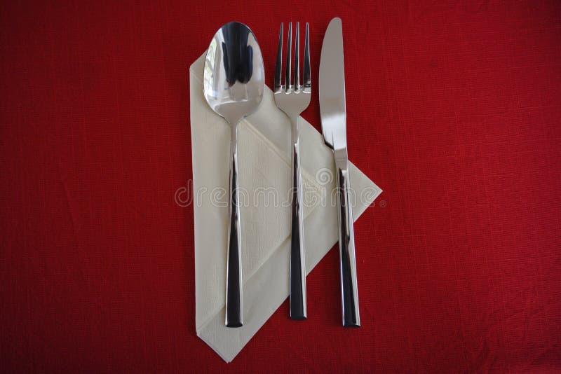 Colher, forquilha e faca em um guardanapo de papel e uma toalha de mesa vermelha, grupo da tabela com espaço da cópia, opinião de imagens de stock royalty free