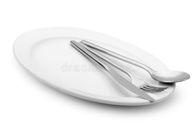 A colher, a forquilha e uma faca encontram-se em uma placa imagens de stock royalty free
