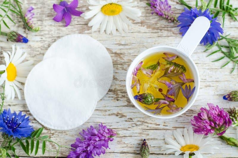 Colher plástica pequena com óleo cosmético do aroma com extratos das flores Ingredientes do cosmético natural fotografia de stock