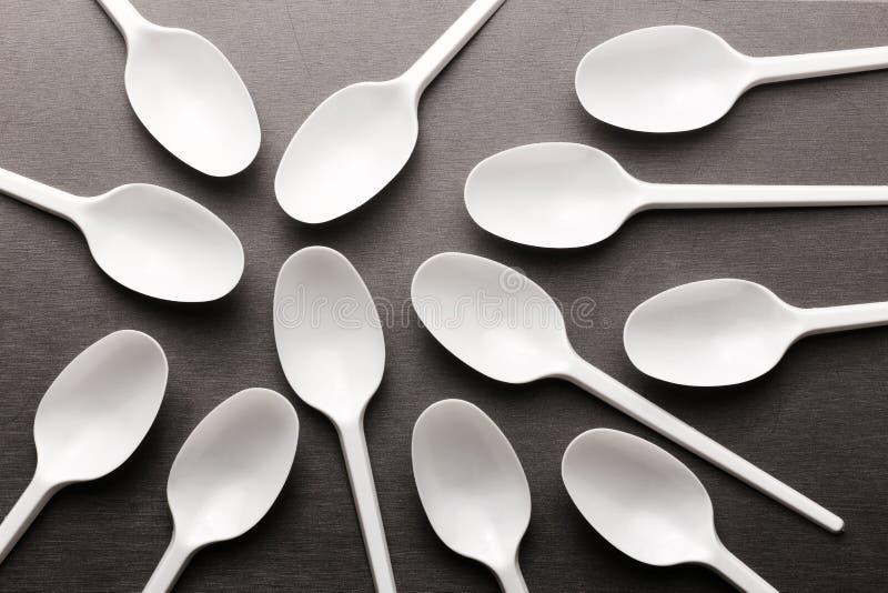 Colheres brancas plásticas descartáveis em um fundo cinzento foto de stock