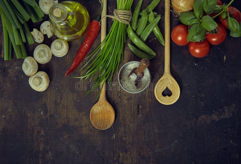 Colheres de madeira com legumes frescos e temperos imagem de stock