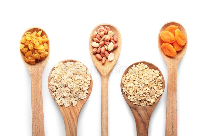 Colheres de madeira com os flocos crus da farinha de aveia, os amendoins e frutos secados no fundo branco foto de stock royalty free