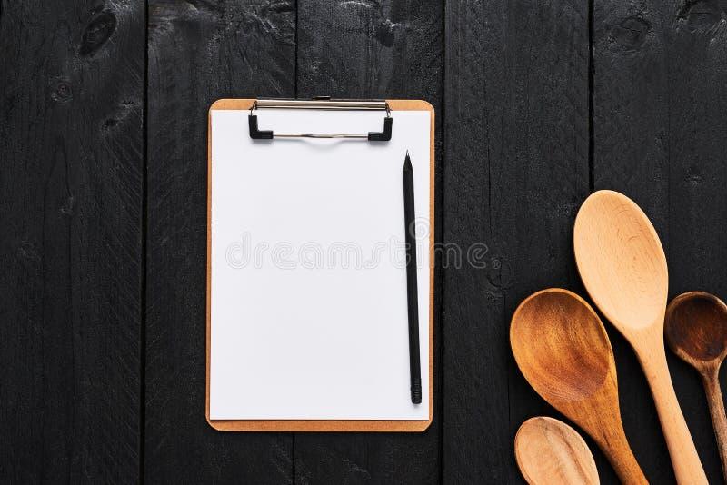 Colheres de madeira com a prancheta vazia do cartão para o menu fotos de stock