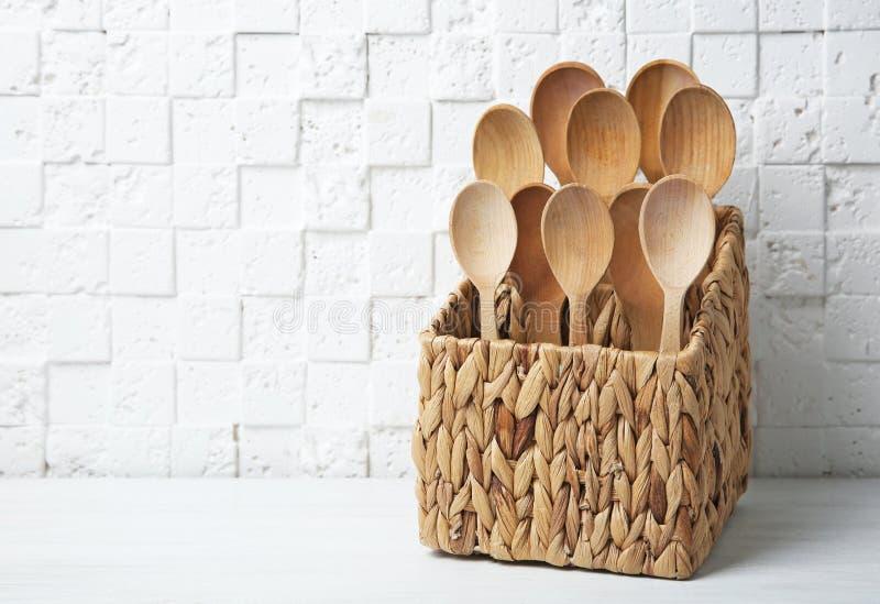 Colheres de madeira na cesta de vime na tabela imagem de stock royalty free