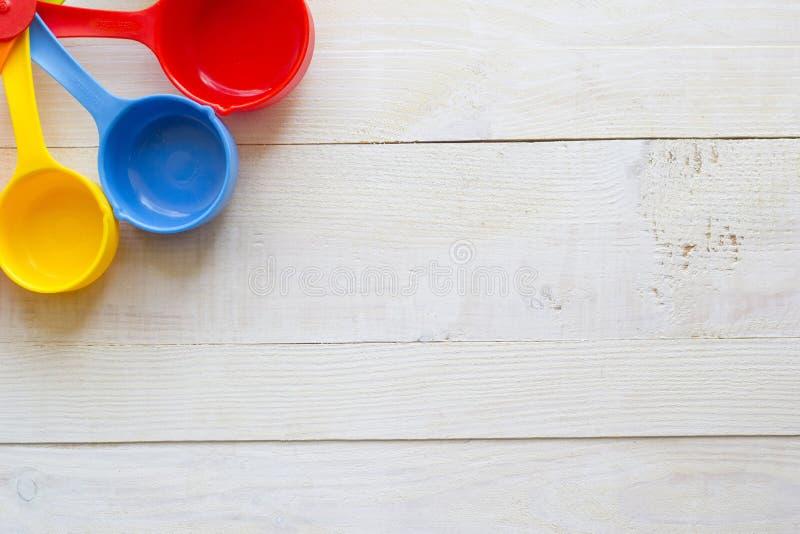 Colheres de medição coloridas para a cozinha em um backgrou de madeira branco foto de stock royalty free