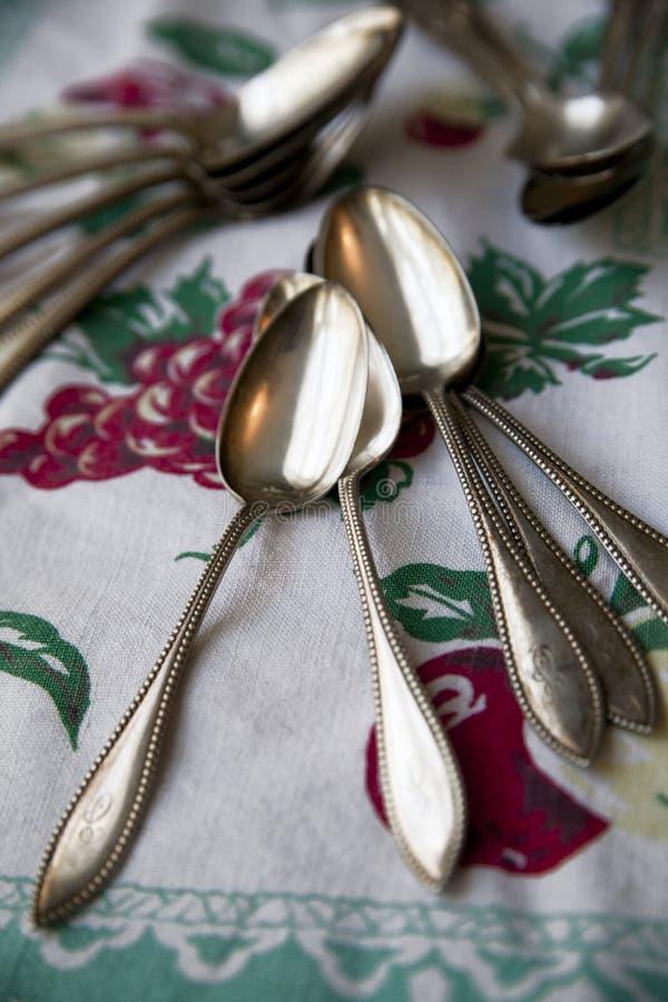 Colheres de prata do vintage em um tablecloth antigo fotos de stock