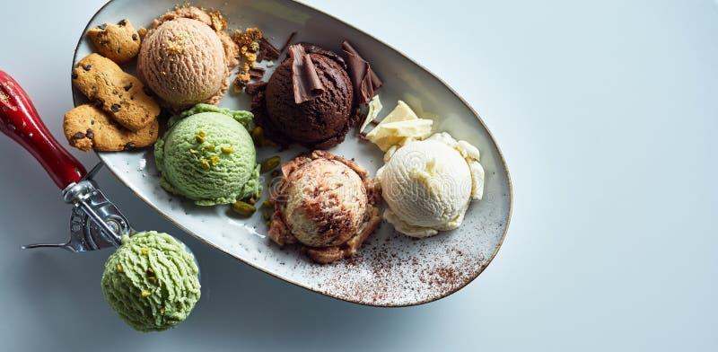 Colheres de sabores sortidos do gelado na bandeja imagens de stock