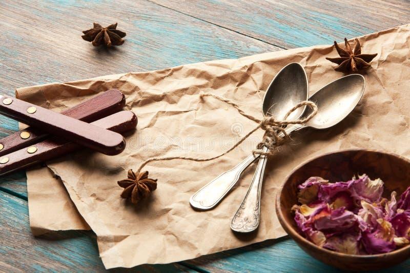 Colheres do chá do vintage e pétalas cor-de-rosa no fundo azul de madeira imagem de stock