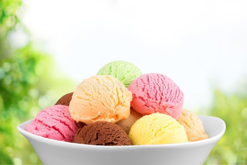 Colheres do gelado na bacia branca fotografia de stock royalty free