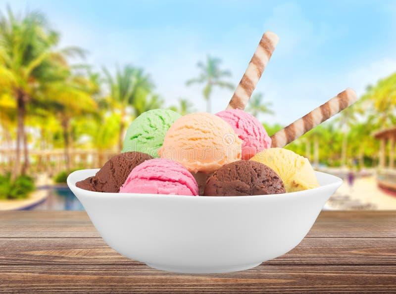 Colheres do gelado na bacia branca fotografia de stock