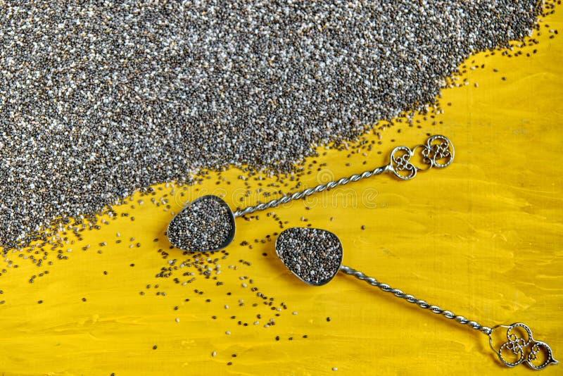 Colheres do vintage com as sementes cruas do chia na placa de madeira amarela O superfood saudável fresco do chia dispersou semen fotos de stock royalty free