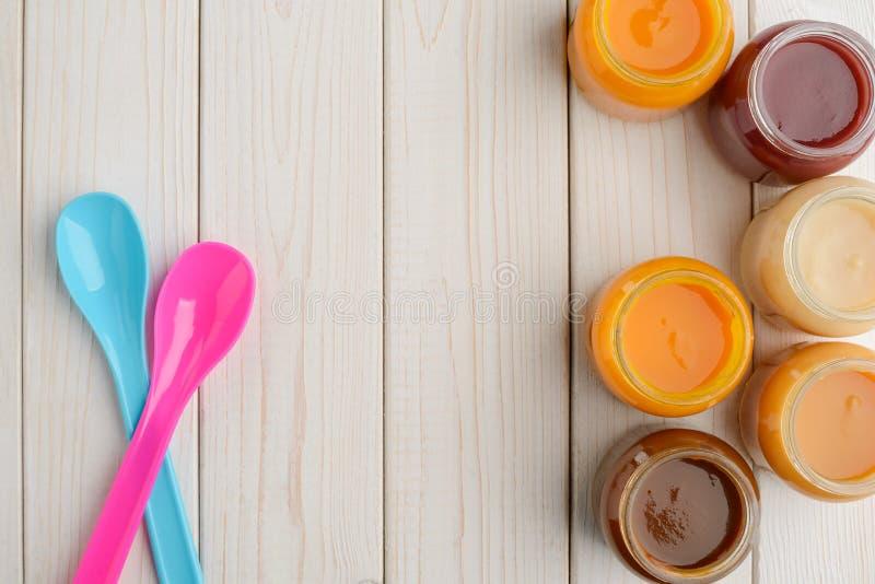 Colheres e frascos do comida para bebê foto de stock royalty free