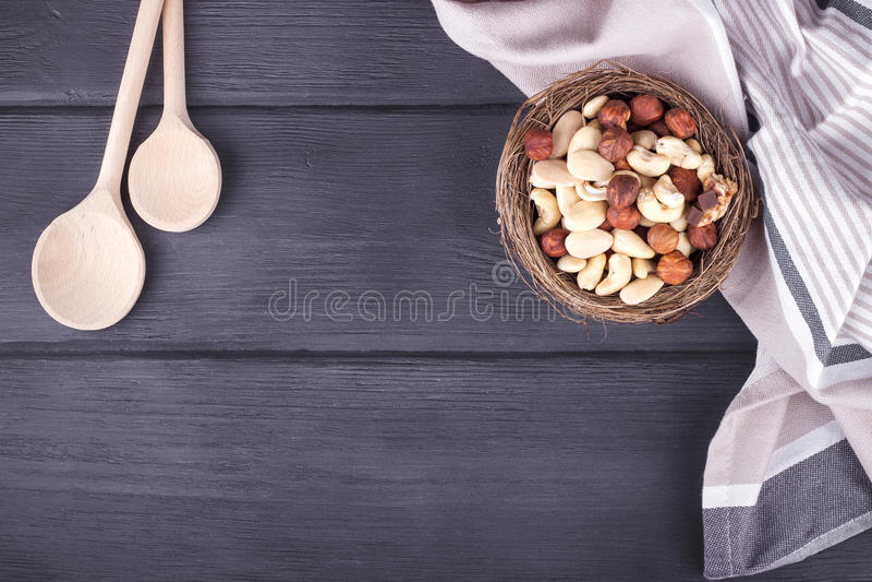 Colheres, toalha de cozinha e bacia de madeira com as porcas misturadas na madeira fotos de stock