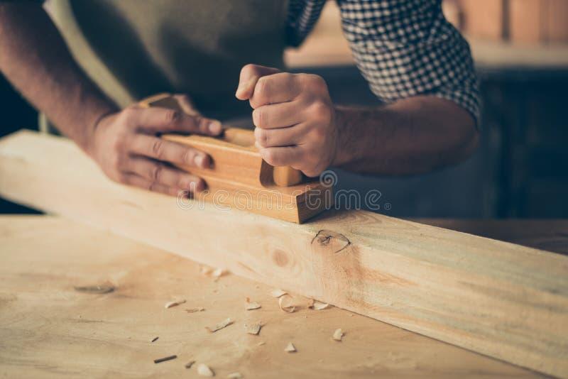 Colhido perto acima da foto do ` s do handicraftsman entrega a fatura de um de madeira foto de stock royalty free