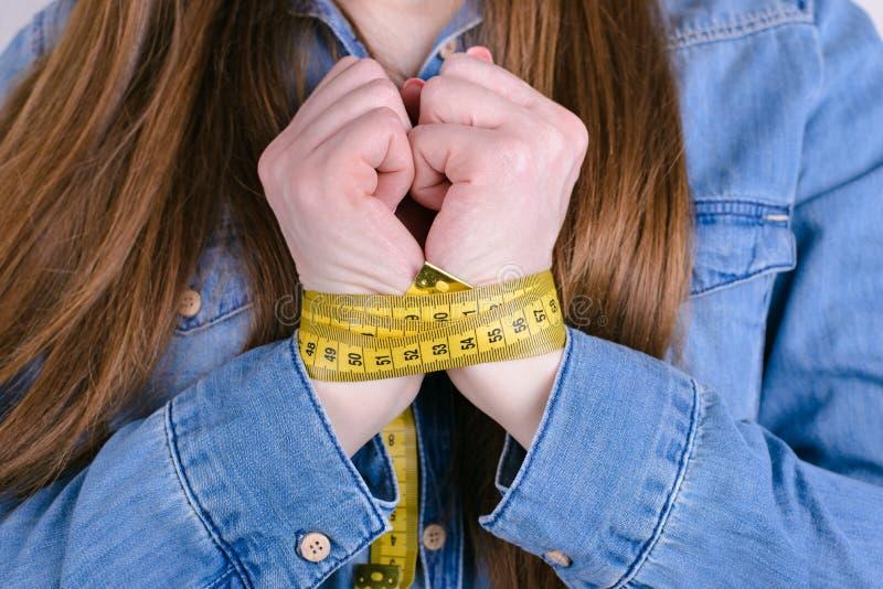 Colhido perto acima da foto da senhora virada triste infeliz que mostra demonstrando as mãos amarradas perto da caixa na camisa o imagens de stock