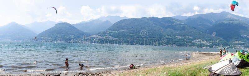 Colico, Italia - 21 luglio 2019: Vista panoramica della spiaggia nel lago Como Kitesurfer che fa un trucco, bambini che giocano s fotografia stock libera da diritti