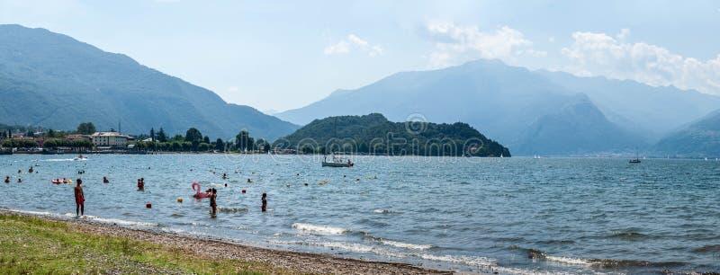 Colico Włochy, Lipiec, - 21, 2019: Panoramiczny widok plaża w Colico, Como jeziora okręg Cypel, Alp góry na tle obrazy royalty free