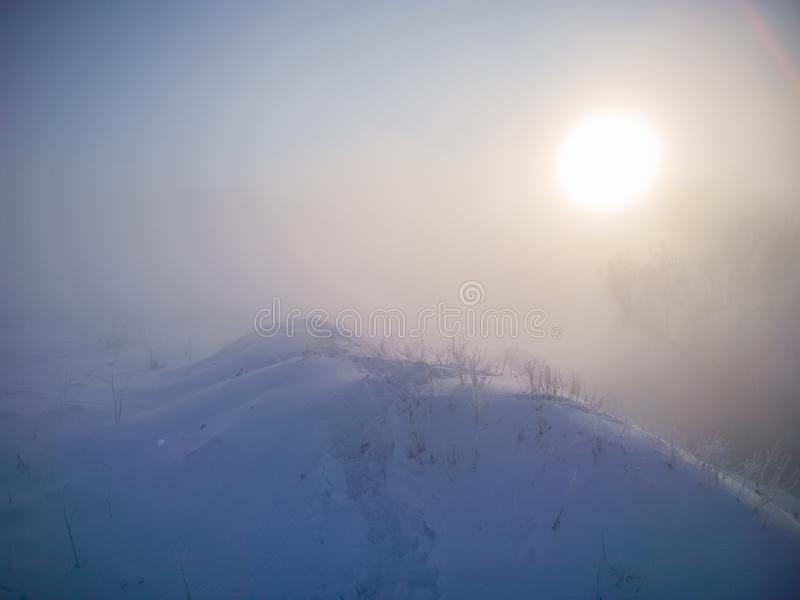 Colina de la nieve del invierno con huellas en nieve profunda en la mañana de niebla imagenes de archivo