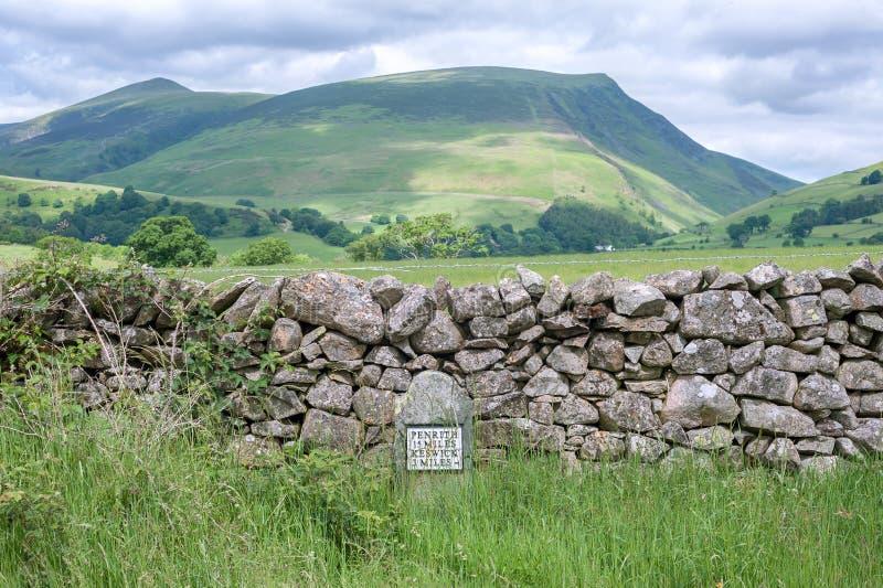 Colinas de Cumbrian con un jalón antiguo y una pared drystone en el primero plano, Cumbria, Reino Unido imagen de archivo