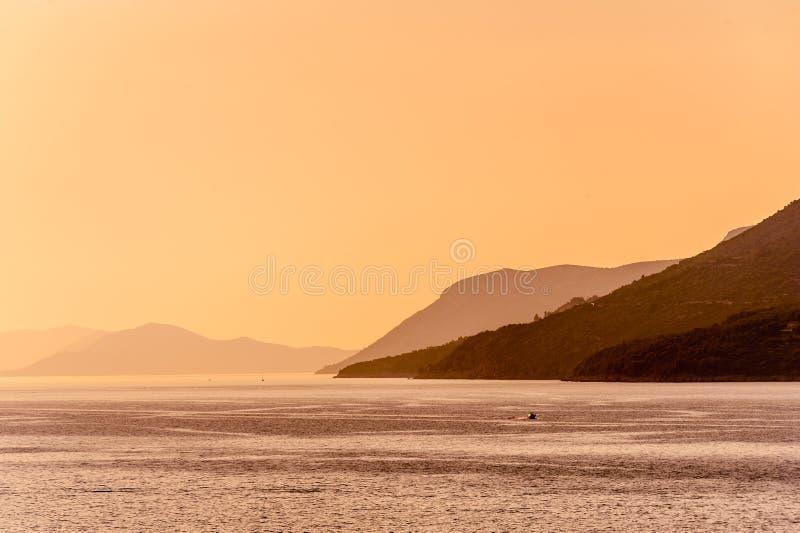 Colinas distantes en niebla de la mañana a través del mar imagenes de archivo