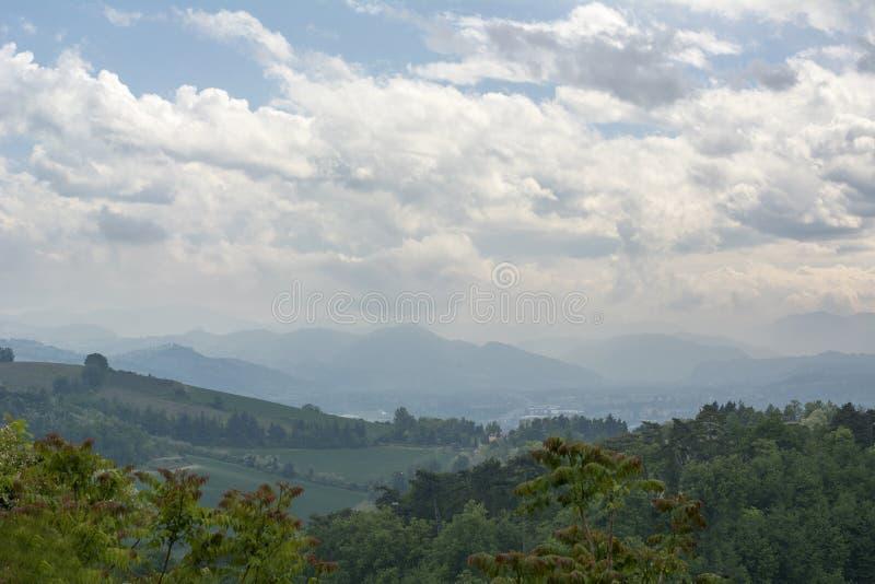 Colinas italianas verdes debajo del cielo nublado en el día imagenes de archivo