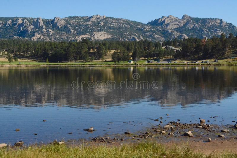 Colinas rocosas que reflejan en el lago Estes imagenes de archivo