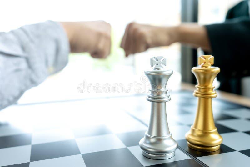 Colisão do punho do homem de negócios perto da cor da prata e do ouro da placa de xadrez na mesa de escritório fotografia de stock